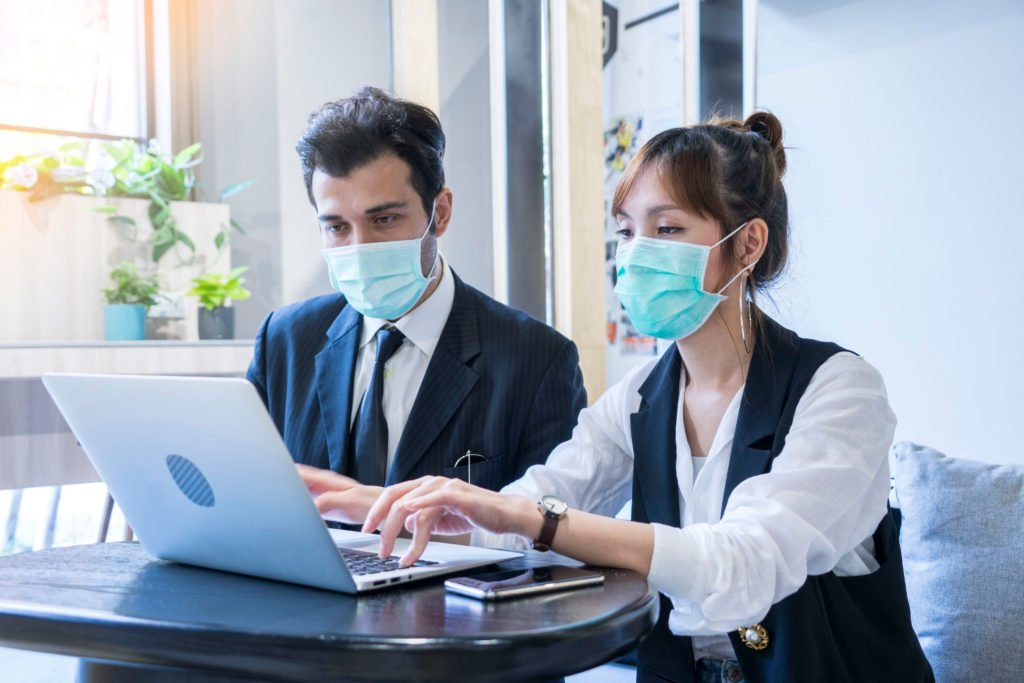 two employees in front of laptop work on Employee Leave Policy