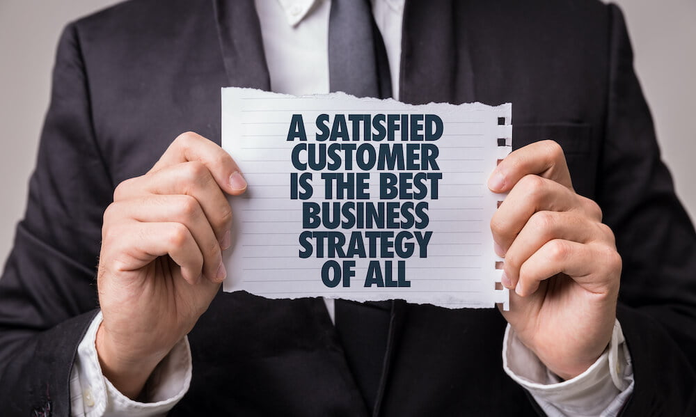 man holding paper that says A satisfied customer is the best business strategy of all