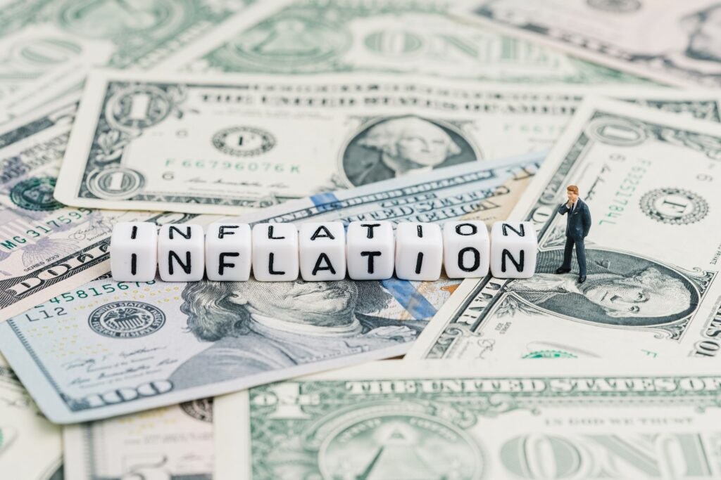 block letters on top of money spelling inflation as graphic for article on how to hedge against increasing inflation